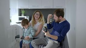 Familia moderna, mamá con el hijo y el papá que juegan en el videojuego que se sienta en silla almacen de video