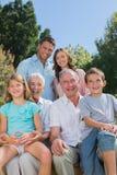 Familia multi alegre de la generación que se sienta en un banco en parque Imagenes de archivo