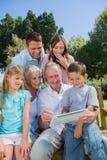 Familia multi de la generación con una PC de la tableta que se sienta en parque Foto de archivo libre de regalías