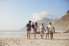 Familia multi de la generación el vacaciones que camina a lo largo de la playa junto foto de archivo