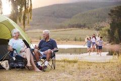 Familia multi de la generación en acampada por el lago junto fotos de archivo libres de regalías