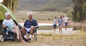 Familia multi de la generación en acampada por el lago junto fotografía de archivo libre de regalías