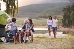 Familia multi de la generación en acampada por el lago junto foto de archivo