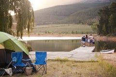 Familia multi de la generación en soporte de la acampada en el embarcadero por el lago fotografía de archivo