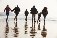 Familia multi de la generación que camina en la playa del invierno fotos de archivo libres de regalías