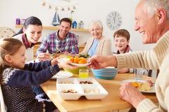 Familia multi de la generación que come el almuerzo en la tabla de cocina Foto de archivo libre de regalías
