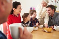 Familia multi de la generación que come el almuerzo en la tabla de cocina fotos de archivo