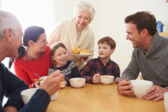 Familia multi de la generación que come el almuerzo en la tabla de cocina foto de archivo