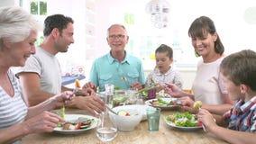 Familia multi de la generación que come la comida alrededor de la tabla de cocina