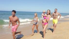 Familia multi de la generación que corre a lo largo de la playa metrajes