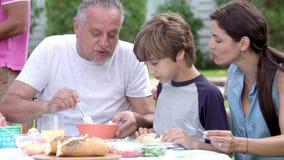 Familia multi de la generación que disfruta de la comida en jardín junto almacen de video