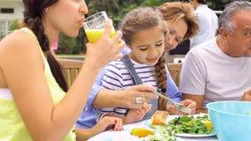 Familia multi de la generación que disfruta de la comida en jardín junto metrajes