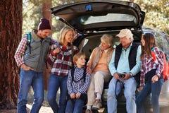 Familia multi de la generación que hace una pausa un coche antes de alza del bosque Foto de archivo
