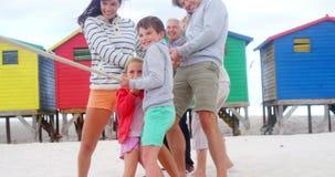 Familia multi de la generación que juega esfuerzo supremo en la playa metrajes