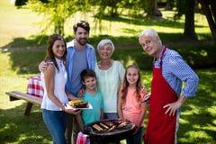 Familia multi de la generación que se coloca cerca de la barbacoa en parque fotografía de archivo libre de regalías