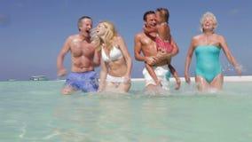 Familia multi de la generación que se divierte en el mar el día de fiesta de la playa metrajes