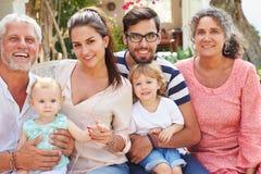 Familia multi de la generación que se sienta al aire libre en casa junto imagen de archivo libre de regalías