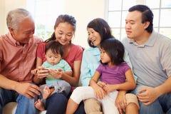 Familia multi de la generación que se sienta en Sofa With Mobile Phone Fotografía de archivo
