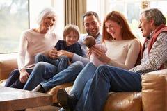 Familia multi de la generación que se sienta en Sofa With Newborn Baby Imágenes de archivo libres de regalías