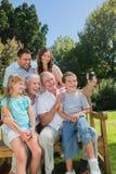 Familia multi de la generación que se sienta en un banco que toma la foto de thems Imagen de archivo
