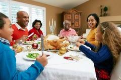 Familia multi de la generación que tiene comida de la Navidad imagenes de archivo