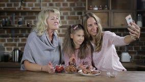 Familia multi de la generación que toma imágenes en cocina metrajes