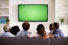 Familia multi de la generación que ve la TV en casa, visión trasera imágenes de archivo libres de regalías