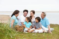 Familia multi de la generación que tiene comida campestre por el mar Imagenes de archivo