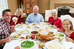 Familia multi de la generación que tiene comida de la Navidad Foto de archivo libre de regalías