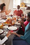 Familia multi de la raza mixta de la generación que lleva a cabo las manos y que dice tolerancia antes de comer en su tabla de ce fotos de archivo libres de regalías