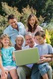 Familia multi feliz de la generación con un ordenador portátil que se sienta en parque Fotos de archivo libres de regalías