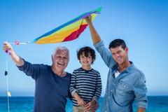 Familia multi feliz de la generación que juega con una cometa Fotografía de archivo libre de regalías