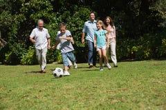 Familia multi feliz de la generación que juega a fútbol Imagenes de archivo
