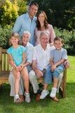 Familia multi feliz de la generación que se sienta en el parque Imagen de archivo