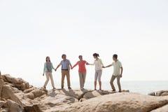 familia Multi-generacional que lleva a cabo las manos en rocas por el mar Imagen de archivo libre de regalías