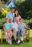 Familia multi sonriente de la generación que se sienta en un banco en parque Foto de archivo