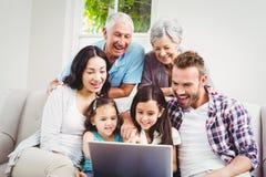 Familia multi sonriente de la generación usando el ordenador portátil fotos de archivo