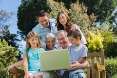 Familia multi sonriente de la generación con un ordenador portátil que se sienta en parque Imagenes de archivo