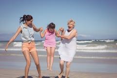 Familia multigeneración alegre que juega en la playa Fotografía de archivo