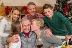 Familia multigeneración con la niña que besa a su abuelo Fotografía de archivo