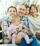 Familia multigeneración en banco en parque del verano Imagen de archivo libre de regalías