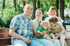 Familia multigeneración feliz de cinco que se sientan en banco Foto de archivo libre de regalías