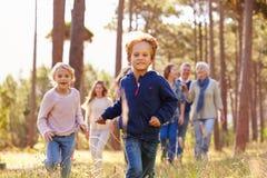 Familia multigeneración que camina en el campo, funcionamiento de los niños Imágenes de archivo libres de regalías