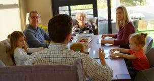 Familia multigeneración que obra recíprocamente con uno a en la mesa de comedor 4k almacen de metraje de vídeo