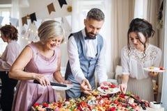 Familia multigeneración que pone la comida en las placas en una fiesta de cumpleaños interior de la familia fotos de archivo libres de regalías