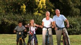 Familia multigeneración que presenta en un parque con sus bicicletas metrajes