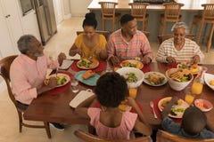 Familia multigeneración que tiene comida junto en la mesa de comedor foto de archivo libre de regalías