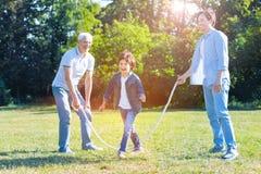 Familia multigenerational radiante que se divierte con la cuerda de salto Fotos de archivo