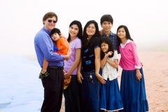 Familia multirracial de siete en la playa de niebla Imagenes de archivo