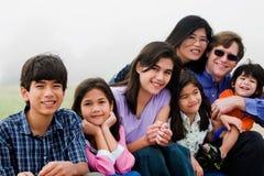 Familia multirracial de siete que se sientan en la playa Fotos de archivo libres de regalías